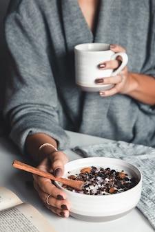 Uma jovem bebe café da manhã, toma um café da manhã saudável e lê um livro.