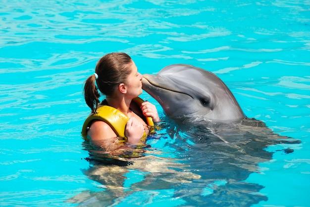 Uma jovem beijando um golfinho na água da turquesa
