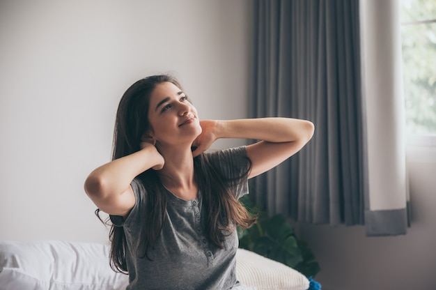 Uma jovem bela caucasiana de cabelos castanhos compridos mulheres desfrutar o momento na cama pela manhã, sorrindo, espreguiçando-se na cama, pessoa de manhã, ralaxing na cama.