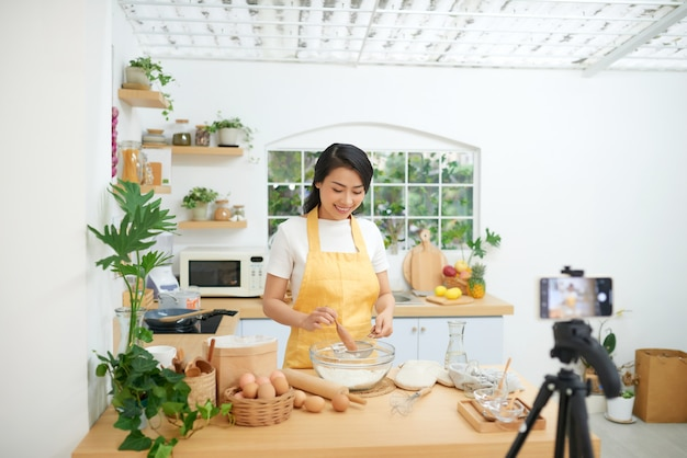 Uma jovem blogueira de culinária asiática trabalhando em um novo vídeo e explicando como cozinhar um prato