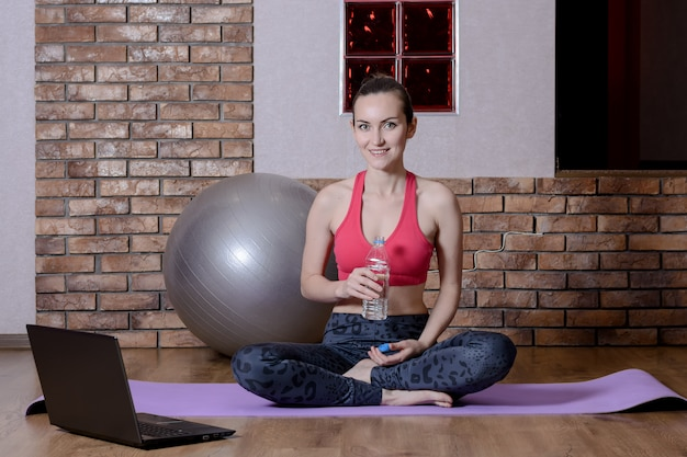 Uma jovem blogueira de esportes está descansando depois de um treino online, bebendo água de uma garrafa de plástico no tapete de ioga. fitness em casa