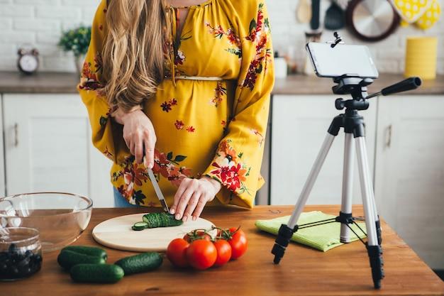 Uma jovem blogueira grávida grava um vídeo de uma receita de salada em uma câmera de smartphone