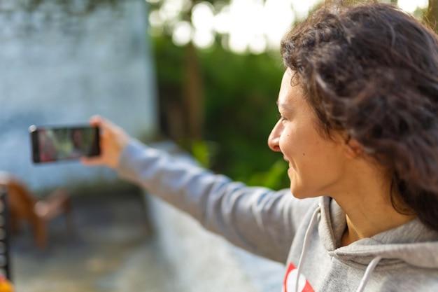 Uma jovem blogueira tira fotos de si mesma com um telefone. relatório de vídeo do blogger.