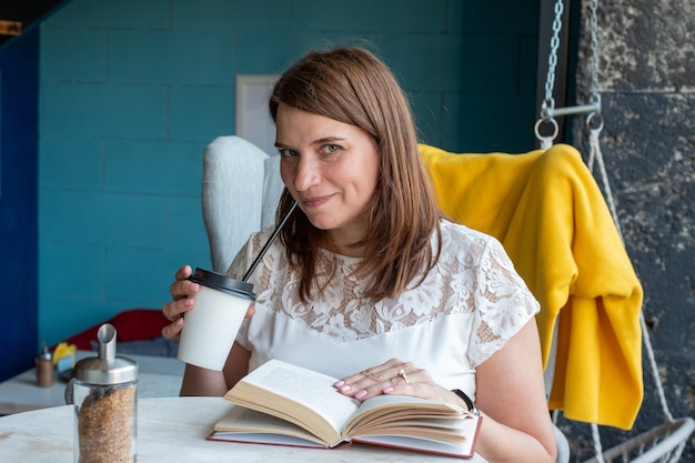 Uma jovem bonita com cabelo comprido ruivo e uma blusa branca está sentada em uma cadeira em um café sozinha, bebe café em um copo de papel com um canudo e lê um livro