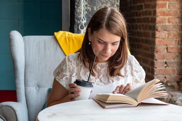 Uma jovem bonita com cabelo comprido ruivo e uma blusa branca sentada em uma cadeira em um café sozinha