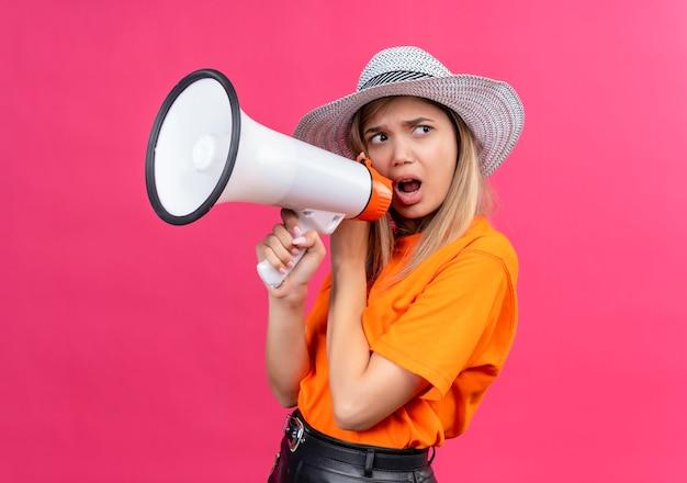 Uma jovem bonita com raiva em uma camiseta laranja usando chapéu de sol falando através do megafone