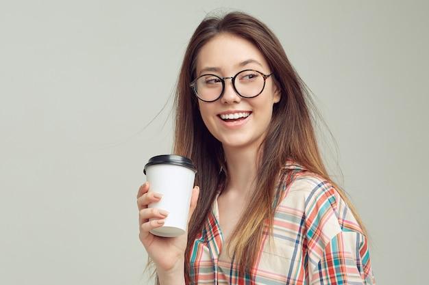 Uma jovem bonita, com roupas casuais, sorri docemente e segura um copo de café em um pacote descartável.
