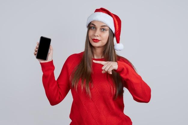 Uma jovem bonita com um chapéu de papai noel, com um telefone nas mãos, aponta o dedo para a tela. conceito de compras online, saudações online, descontos de natal.