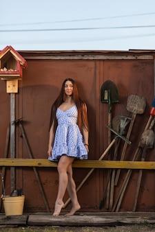 Uma jovem bonita de cabelos escuros com um short de verão demonstra seu corpo atlético contra o fundo de uma cerca ao lado de ferramentas de verão, pás ancinhos o conceito de férias de verão