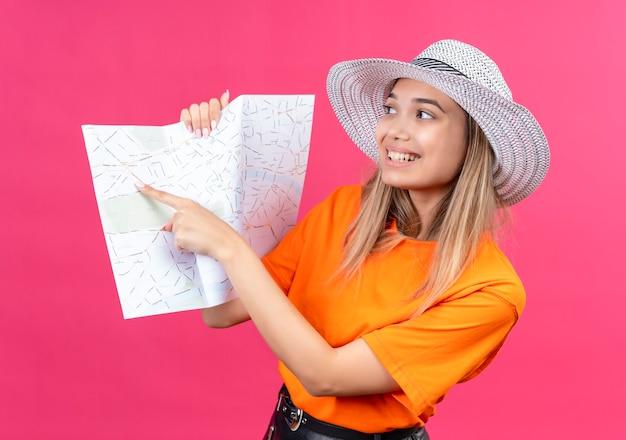 Uma jovem bonita e feliz com uma camiseta laranja e chapéu de sol apontando para um mapa com o dedo indicador em uma parede rosa