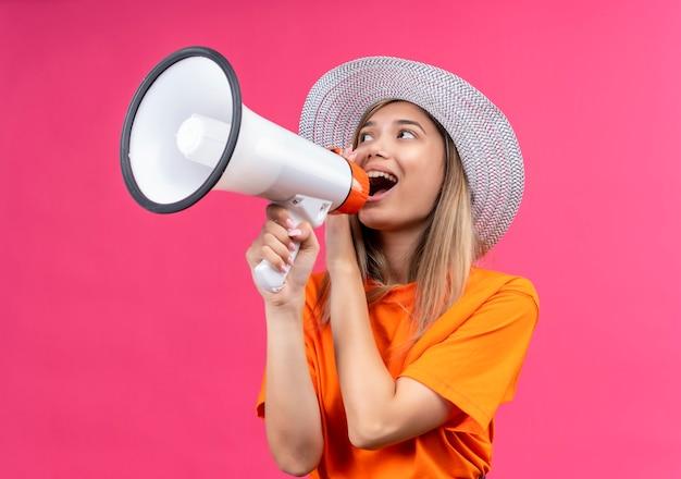 Uma jovem bonita e feliz com uma camiseta laranja e chapéu de sol falando através de um megafone em uma parede rosa