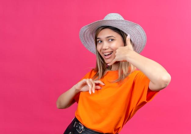 Uma jovem bonita e feliz com uma camiseta laranja e chapéu de sol mostrando um gesto de me ligar enquanto olha de lado em uma parede rosa