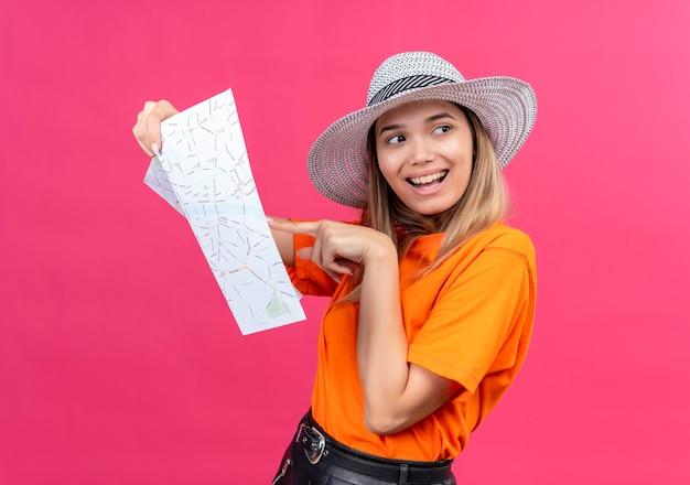 Uma jovem bonita e feliz com uma camiseta laranja e chapéu de sol, sorrindo enquanto aponta para um mapa e olhando de lado em uma parede rosa
