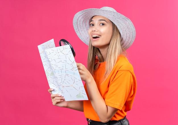 Uma jovem bonita e feliz com uma camiseta laranja usando um chapéu de sol segurando um mapa com uma lupa enquanto olha de lado em uma parede rosa