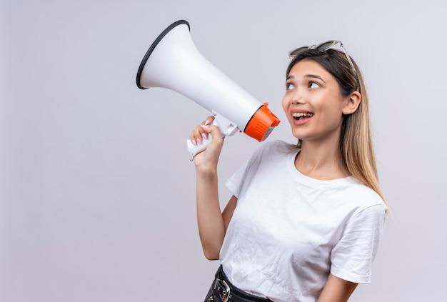 Uma jovem bonita e feliz em uma camiseta branca usando óculos escuros na cabeça falando através de um megafone em uma parede branca