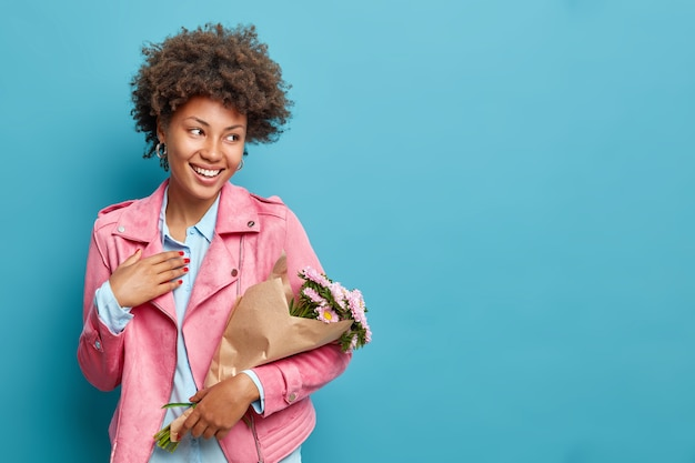Uma jovem bonita e feliz segurando um buquê embrulhado em papel recebe lindas flores e aproveita a primavera e usa uma elegante jaqueta rosa isolada sobre a parede azul