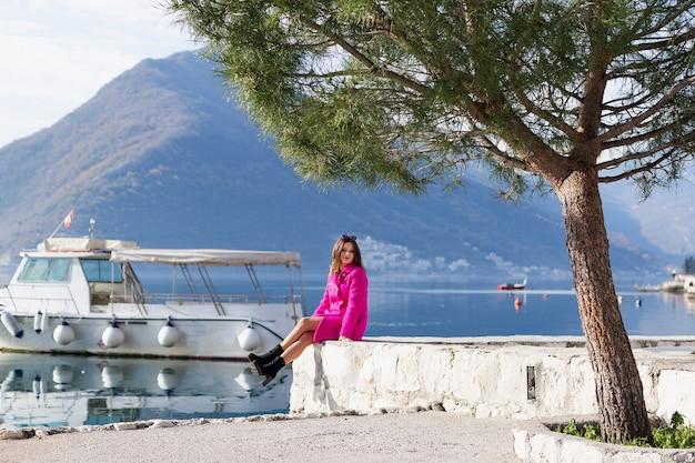 Uma jovem bonita e sorridente aprecia a bela vista do mar. happy senta-se na beira do cais e olha para as montanhas. sozinho com a natureza.