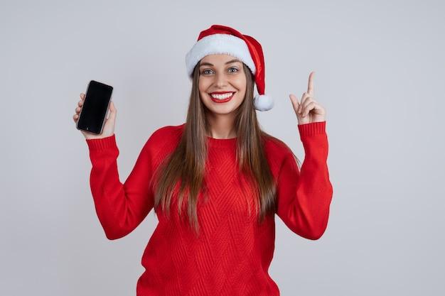 Uma jovem bonita e sorridente com um chapéu de papai noel, com um telefone nas mãos, aponta o dedo para a tela. conceito de compras online, saudações online, descontos de natal.