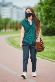 Uma jovem bonita em uma máscara médica azul marinho caminha segurando uma bolsa de couro no parque