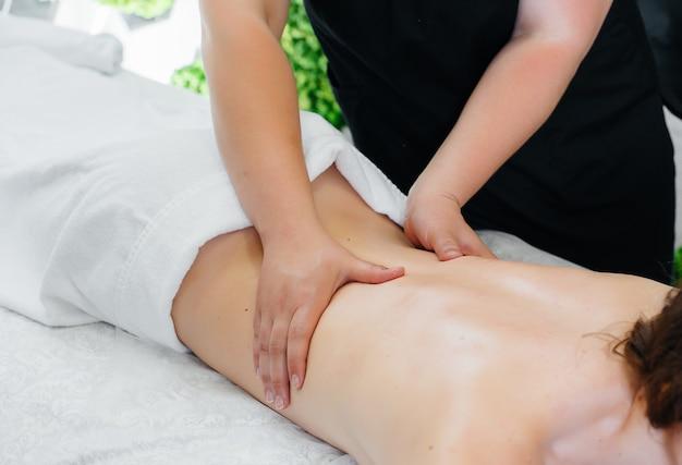 Uma jovem bonita está desfrutando de uma massagem cosmetológica profissional no spa.