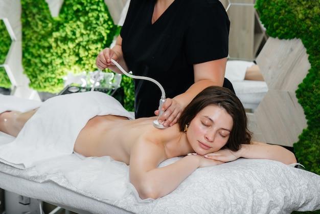 Uma jovem bonita está desfrutando de uma massagem profissional a vácuo no spa. cuidado do corpo. salão de beleza.