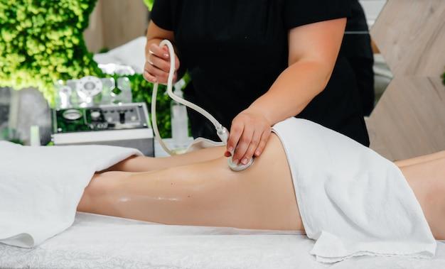 Uma jovem bonita está desfrutando de uma massagem profissional a vácuo no spa.