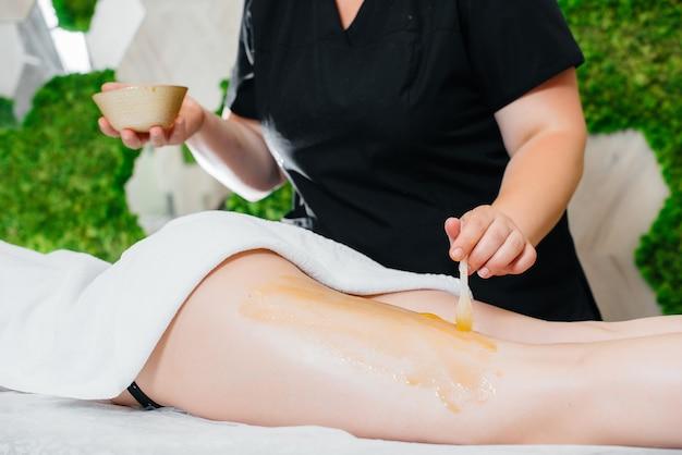Uma jovem bonita está desfrutando de uma massagem profissional com mel no spa. cuidado do corpo. salão de beleza.