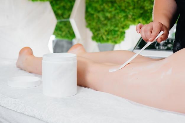 Uma jovem bonita está desfrutando de uma massagem profissional com mel no spa.
