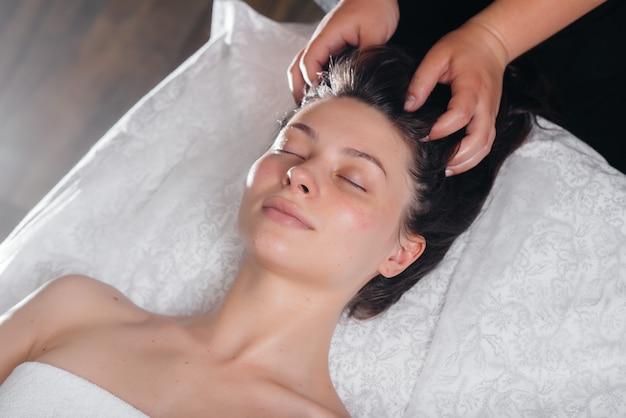 Uma jovem bonita está desfrutando de uma massagem profissional na cabeça no spa. cuidado do corpo. salão de beleza.
