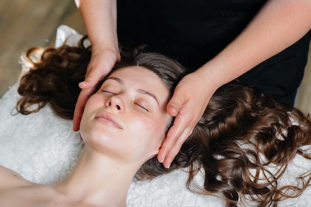 Uma jovem bonita está desfrutando de uma massagem profissional na cabeça no spa.