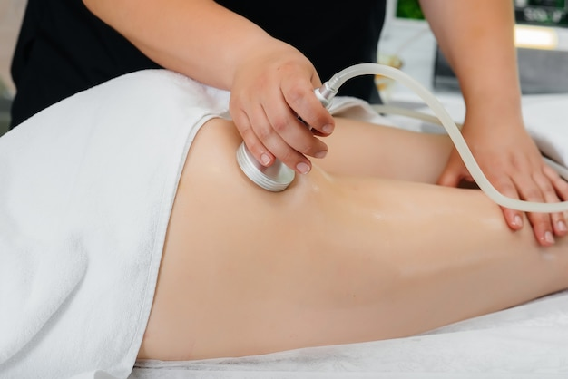Uma jovem bonita está fazendo uma massagem profissional a vácuo no spa