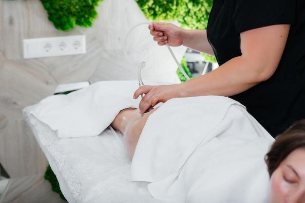 Uma jovem bonita está fazendo uma massagem profissional a vácuo no spa Foto Premium