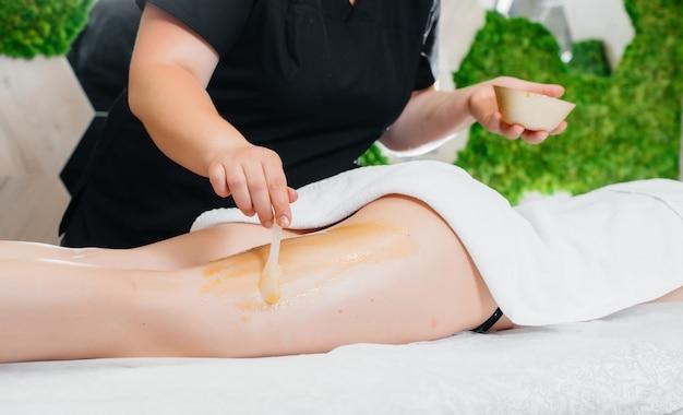 Uma jovem bonita está fazendo uma massagem profissional com mel no spa Foto Premium