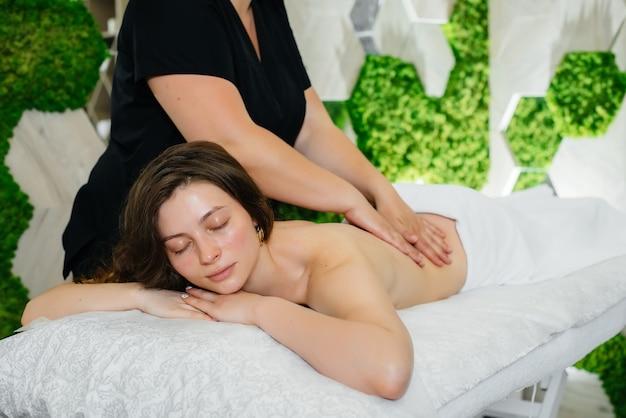 Uma jovem bonita está recebendo uma massagem cosmetológica profissional no spa