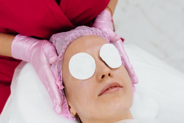 Uma jovem bonita está recebendo uma massagem profissional na cabeça no spa
