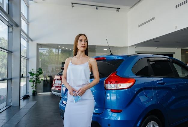 Uma jovem bonita inspeciona um carro novo em uma concessionária de automóveis.