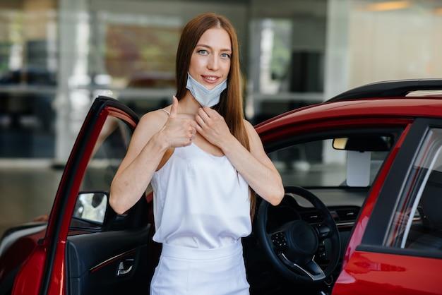 Uma jovem bonita inspeciona um carro novo em uma concessionária de veículos com uma máscara durante a pandemia. a venda e compra de automóveis, no período de pandemia.