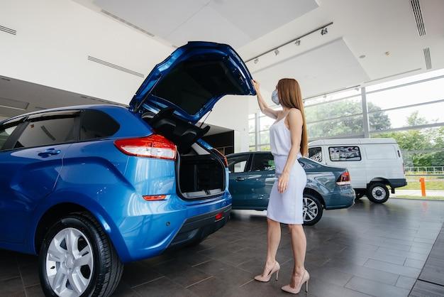 Uma jovem bonita inspeciona um carro novo em uma concessionária de veículos com uma máscara durante a pandemia.