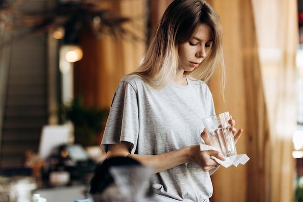 Uma jovem bonita loira, vestida em estilo casual, segura um copo limpo e olha para ele em um café moderno. .