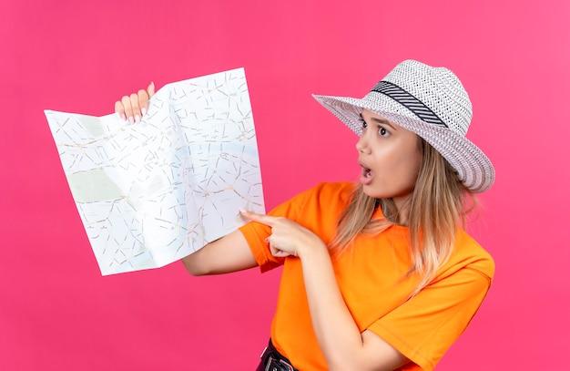 Uma jovem bonita surpresa com uma camiseta laranja e chapéu de sol apontando para um mapa com o dedo indicador em uma parede rosa