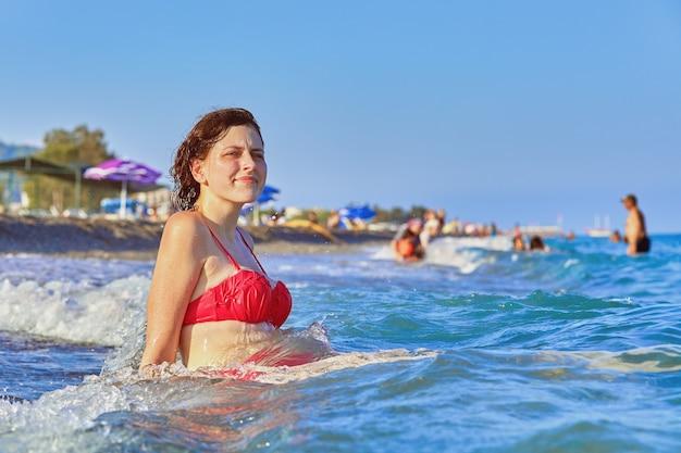 Uma jovem branca de cerca de 20 anos em um maiô vermelho está sentada na praia, tomando banho de sol.