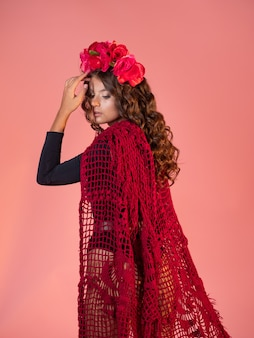 Uma jovem brilhante e ousada com rosas na cabeça e uma capa vermelha de tricô