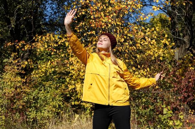 Uma jovem brilhante em uma capa de chuva amarela e um chapéu cor de vinho no contexto das folhas de outono amarelas e céu azul.