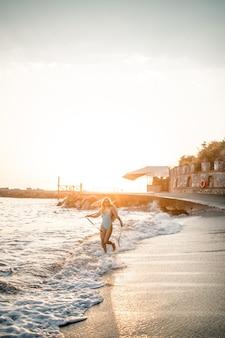 Uma jovem bronzeada em um lindo maiô com chapéu de palha se levanta e descansa em uma praia tropical com areia e olha o pôr do sol e o mar. foco seletivo. conceito de férias à beira-mar