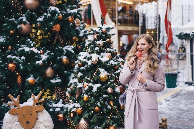Uma jovem caminha no natal na praça perto das árvores de natal decoradas. candy é um pirulito em forma de coração.