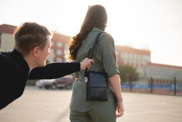 Uma jovem caminhando na rua da cidade e um ladrão tentam roubar sua bolsa, conceito de crime e violência