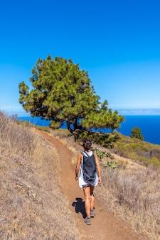 Uma jovem caminhando no caminho de las tricias na cidade de garafia, no norte da ilha de la palma, nas ilhas canárias