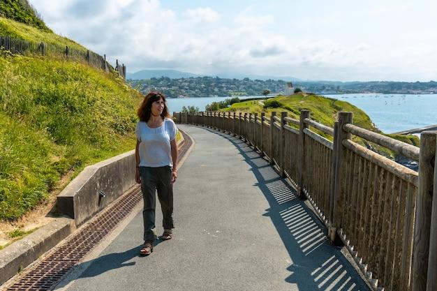 Uma jovem caminhando no parque natural de saint jean de luz chamado parc de sainte barbe, col de la grun no país basco francês