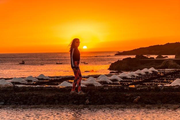 Uma jovem caminhando no pôr do sol alaranjado na salina e ao fundo o farol de fuencaliente na rota dos vulcões ao sul da ilha de la palma, nas ilhas canárias, espanha