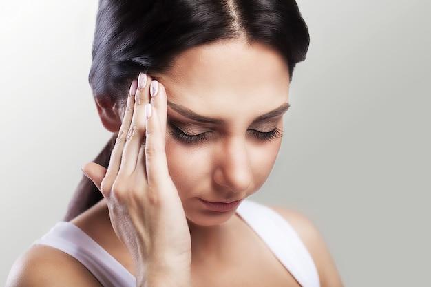 Uma jovem cansada e exausta que sofre de uma forte dor de cabeça de tensão. sofrem de dor de cabeça. enxaqueca